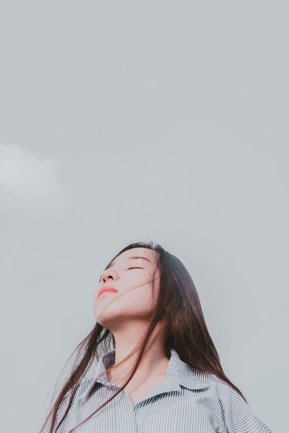 Girl with long hair,looking up into the sky with eyes closed