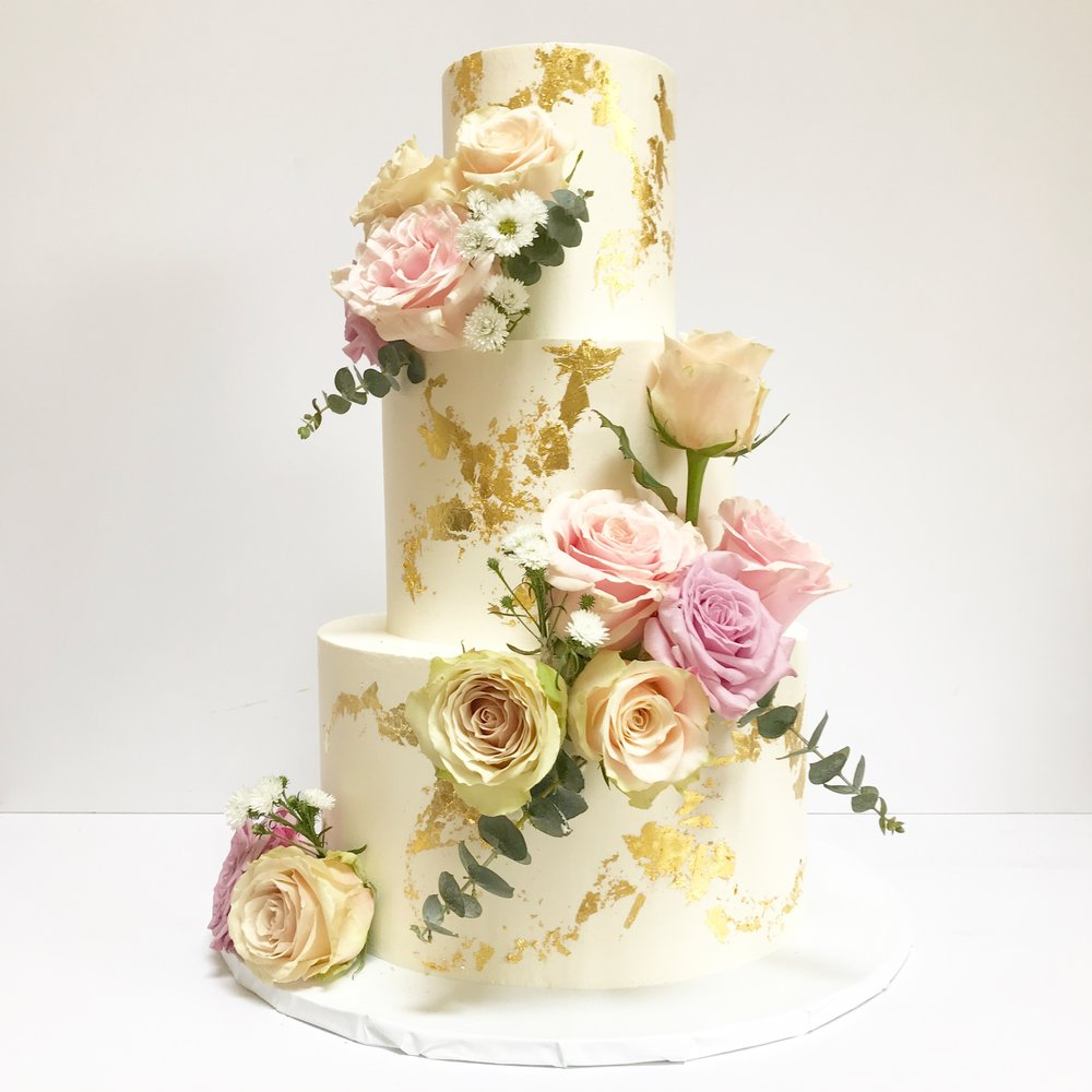 White and gold buttercream wedding cake with flowers.JPG