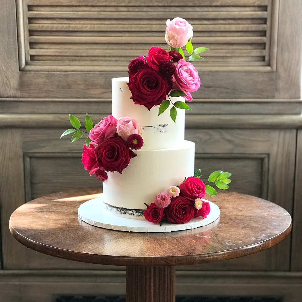 Semi-naked buttercream wedding cake with red flowers.JPG