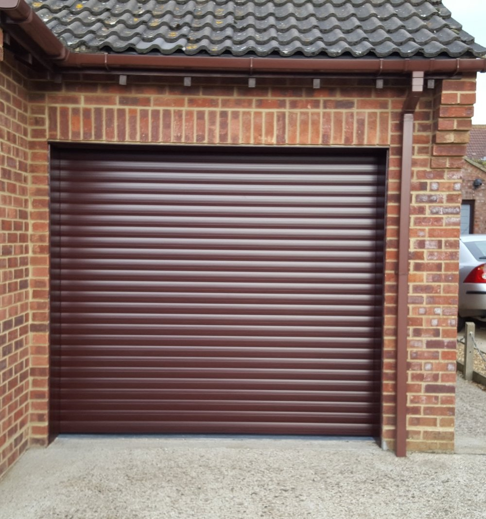 Roller Shutter Garage Doors - Our roller shutter doors are available in a wide range of colours as standard and can be painted anyone of the thousands of RAL colours available for a truly unique finish. Fitted with a remote controlled electronic opening system with a smart safety edge technology preventing the door from shutting in the event of an obstruction. Our  insulated aluminium roller shutter is three times as thick as other inferior alternatives, providing both better security and insulation.