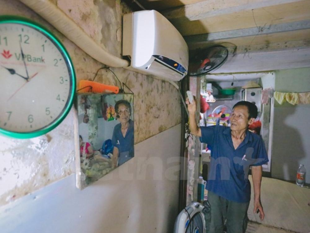 Mỗi ngày, ông lại tự đi thăm hỏi mỗi phòng trọ, đồng thời nhắc nhở mọi người sử dụng điều hòa tiết kiệm trong đợt cao điểm nắng nóng này. (Ảnh: Minh Sơn/Vietnam+)