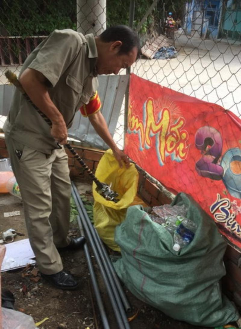 Ve chai, phế liệu thu được ông đem về bỏ ở một góc sân nhà sinh hoạt cộng đồng khu phố 8. Trong ảnh, ông Vũ dùng cây gậy nam châm để gom nắp chai.