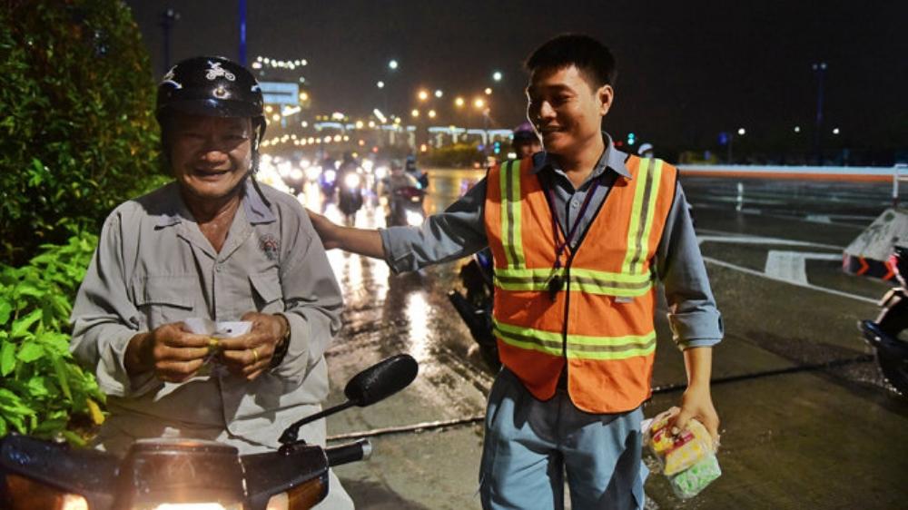 Người dân vui vẻ khi nhận được áo mưa khi trú mưa tại miệng hầm sông Sài Gòn - Ảnh: HỮU THUẬN