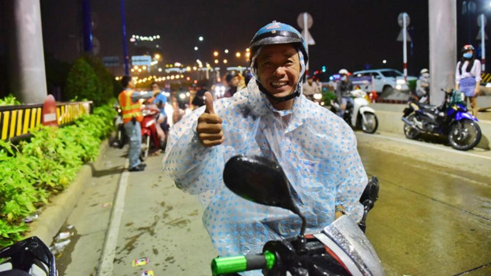 Anh Trương Văn Huân cảm kích khi được tặng áo mưa - Ảnh: HỮU THUẬN