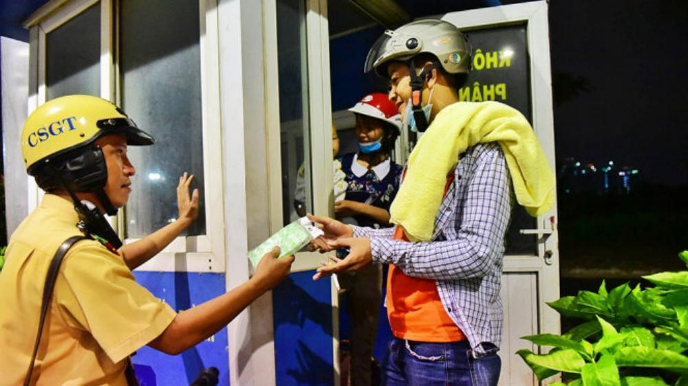 Thượng úy Trần Tuấn Anh thuộc đội CSGT Bến Thành tặng áo mưa cho người dân - Ảnh: HỮU THUẬN