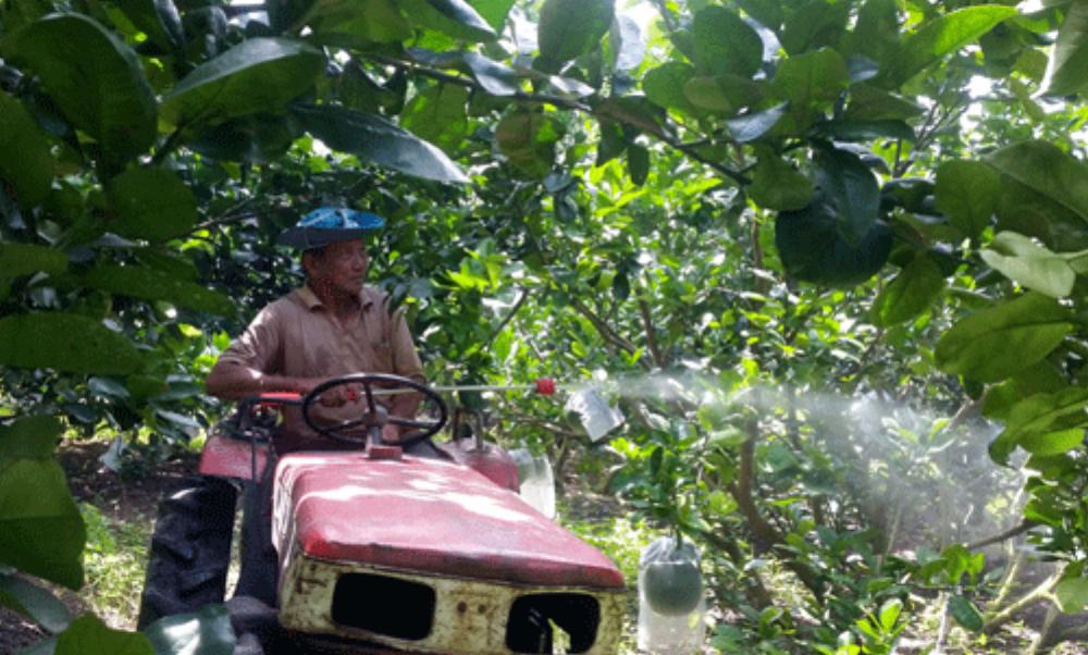 Lão nông Nguyễn Văn Long trên cỗ máy phun thuốc do ông sáng chế.Ảnh: Hồ Văn