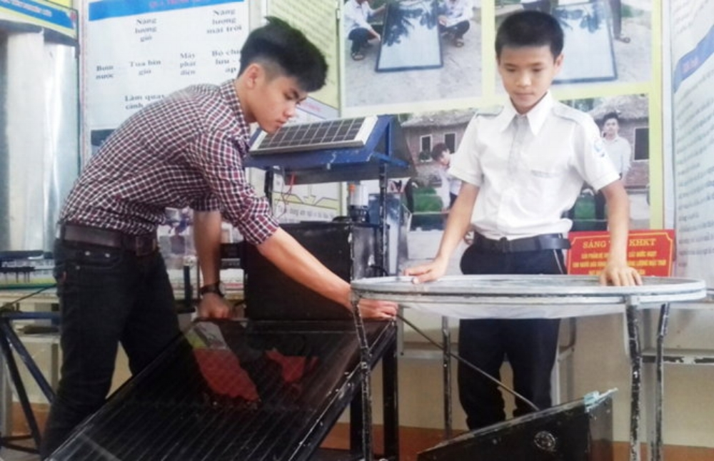 Ngô Thành Đạt (trái) và Nguyễn Tiến Dũng giới thiệu chiếc máy biến nước mặn thành nước ngọt -Ảnh: D.HÒA