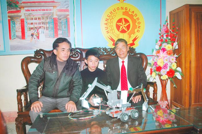 Học sinh Trần Văn Phát (giữa) đang thuyết trình về nguyên lý hoạt động của máy xúc hai tay.