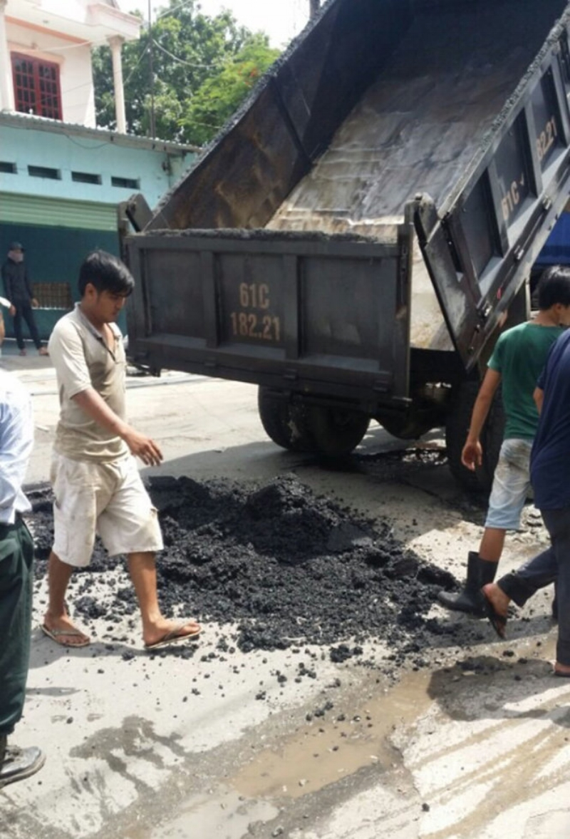 Xe ben đổ nhựa xuống lỗ trũng - Ảnh: Người dân cung cấp