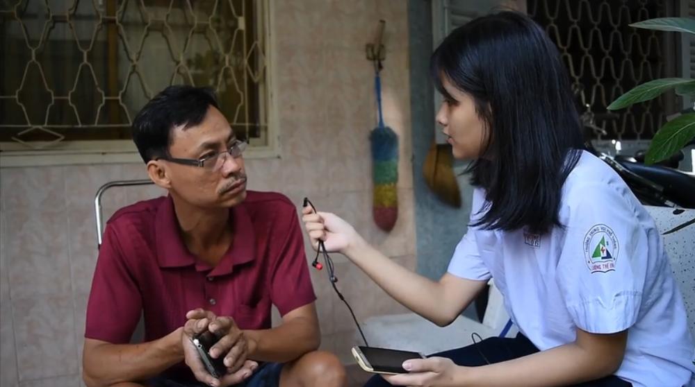 Một học sinh đang phỏng vấn người dân sống trong hẻm.