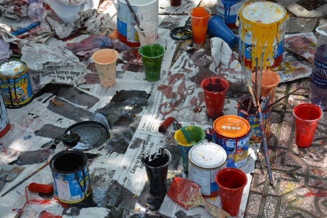 Những lọ sơn được bày ra khắp nơi, sau đó sẽ được dọn dẹp sạch sẽ khi vẽ xong.