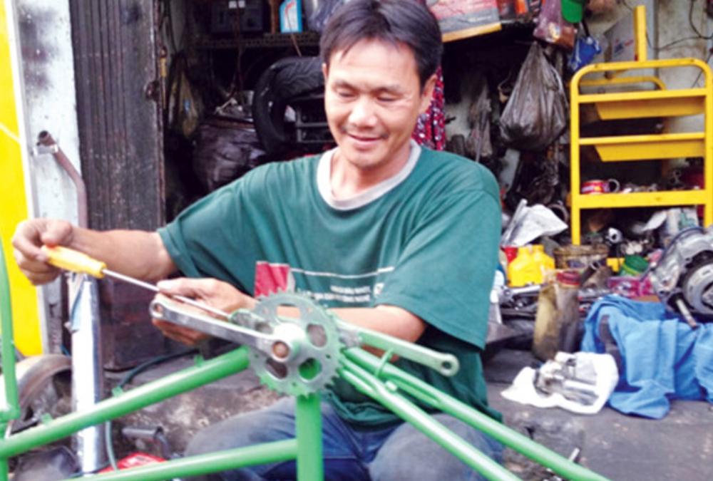 Anh Lê Văn Thái lắp ráp xe đạp cũ tặng người nghèo. Ảnh: Trọng Thịnh.