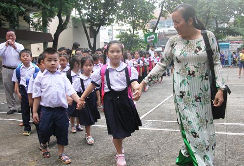 Học sinh lớp một trường Tiểu học Nguyễn Trọng Tuyển, thành phố Hồ Chí Minh được cô giáo dẫn vào lớp (ảnh Mạnh Tùng - Vnexpress)