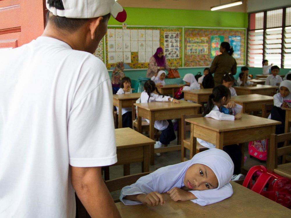 Một em nhỏ Malaysia cảm thấy mệt trong ngày đầu tiên đi học (nguồn: AP Photo/Lim Huey Teng)