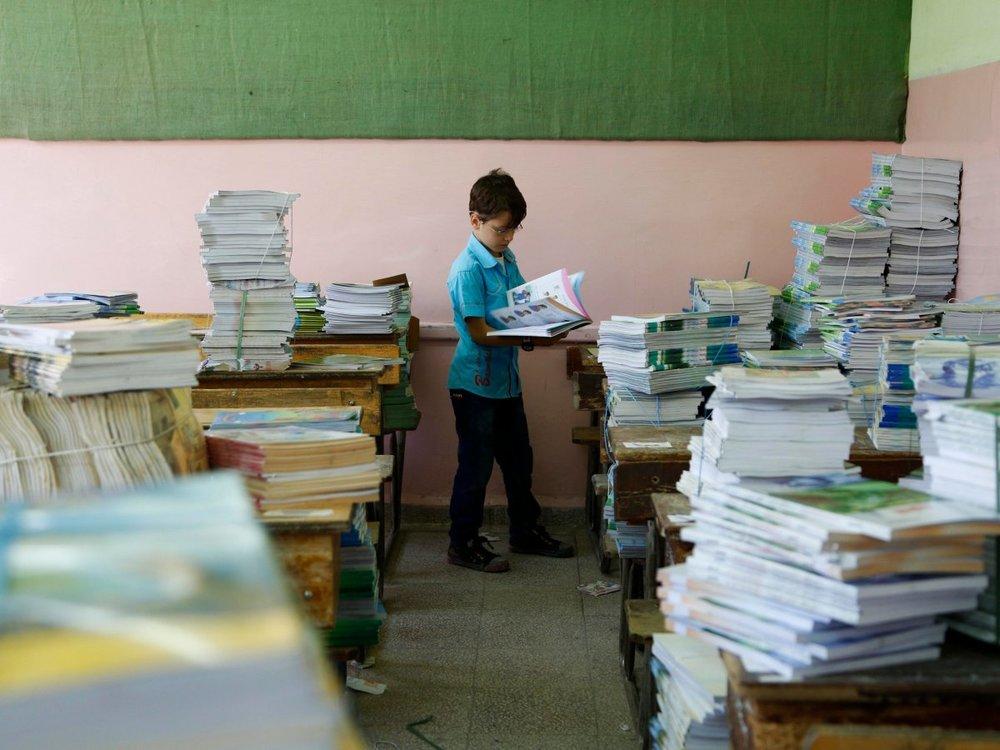 Một em nhỏ Syria nhận sách tại trường (nguồn: REUTERS/Omar Sanadiki)