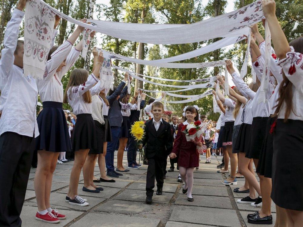 Những anh chị khóa trên đang chào mừng các em mới vào trường tại Ukraine (nguồn: REUTERS/Gleb Garanich)