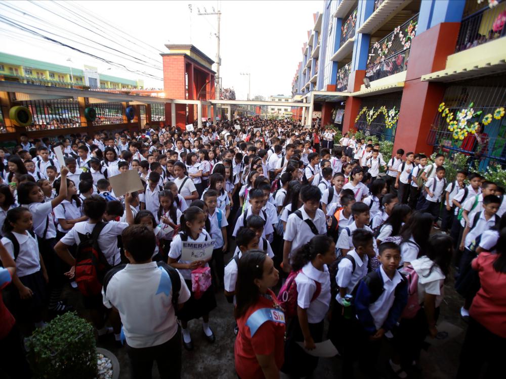 Xếp hàng dưới sân tại một trường tiểu học ở Phi-lip-pin (nguồn: AP Photo/Aaron Favila)
