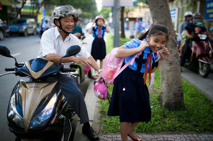 Một em học sinh trường tiểu học Đinh Tiên Hoàng, Hồ Chí Minh vui vẻ khi tới trường (ảnh Hoàng Triều, báo Người lao động)
