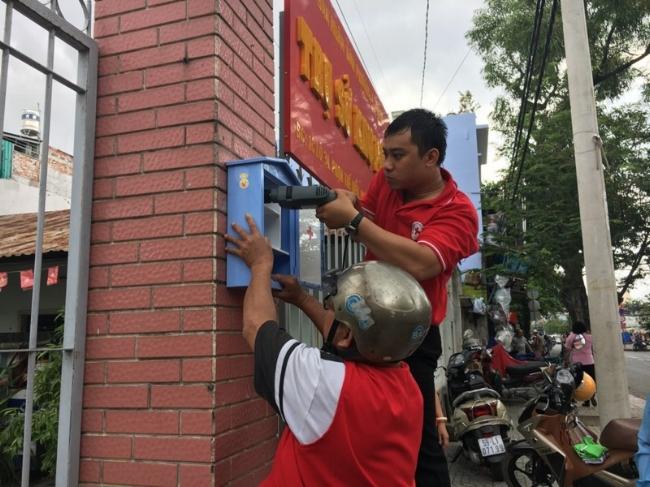 Cán bộ Hội Chữ thập đỏ quận 8 đang gắn tủ sơ cấp cứu miễn phí phía bên ngoài trụ sở khu phố 5, phường 4 trên đường Phạm Thế Hiển.