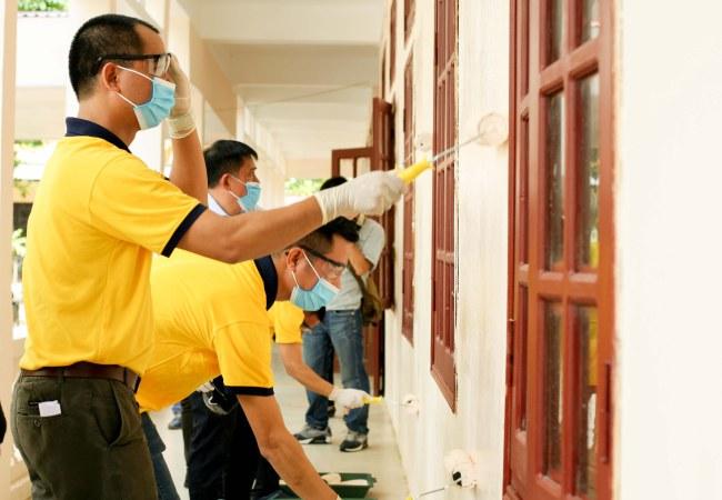 Nhân viên hãng sơn cùng nhau sơn lại các bức tường cũ của nhà trường