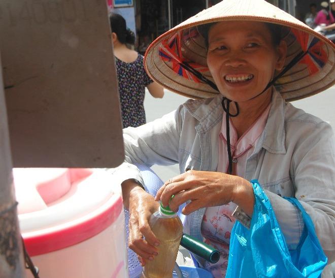 """Với bà Nguyễn Thị Định quê gốc Nam Định, làm nghề mua ve chai, bao nhiêu năm ở Sài Gòn thì cũng chừng ấy năm bà biết ơn thùng nước miễn phí ở góc đường Phan Đình Phùng này. """"Đang cơn trưa nắng mà có chai nước trà đá mát lạnh giải cơn khát thì còn gì quý bằng, mỗi lần uống nước lại thầm cảm ơn ai đã đặt bình nước"""".Bà tìm đến điểm trà đá miễn phí này mỗi ngày 2-3 bận. Có những đêm khuya khoắt, đi ngang nước đá vẫn còn, bà càng ngạc nhiên vì tấm lòng của những người lạ đã cung cấp nước mát 24/24 giờ."""
