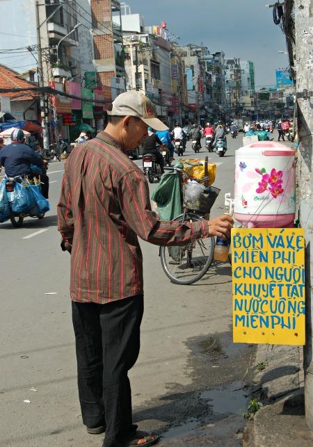 """Ông Hoàng Phương buôn ve chai, đang trọ ở quận Bình Thạnh. Mỗi ngày ông đi qua đường này 4 lần, đều rót chai nước mát giải khát. """"Nhẩm tính sơ thì không có thùng nước, mỗi ngày tốn cả chục nghìn tiền nước, hết ký gạo chứ chẳng đùa"""", ông Phương nói."""
