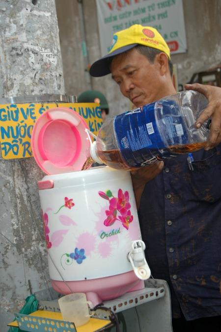 """Bên cạnh tủ thuốc, bình nước trà đá miễn phí được nhiều người đi đường thường xuyên sử dụng. Bình nước do ông Đỗ Văn Út (sinh năm 1963) phụ trách pha trà, thêm đá... từ mấy chục năm nay. Ông Út được bà con trong hẻm ví là """"cây từ thiện"""" bởi đã khởi xướng những hoạt động thiết thực này. Ông Út làm nghề vá xe và chạy xe ôm, miễn phí cho người khuyết tật. Vợ chồng ông ở trọ trong căn phòng diện tích vài mét vuông, điều kiện kinh tế không dư dả nhưng điều đó không ngăn được ông mở lòng chia sẻ với người khác."""