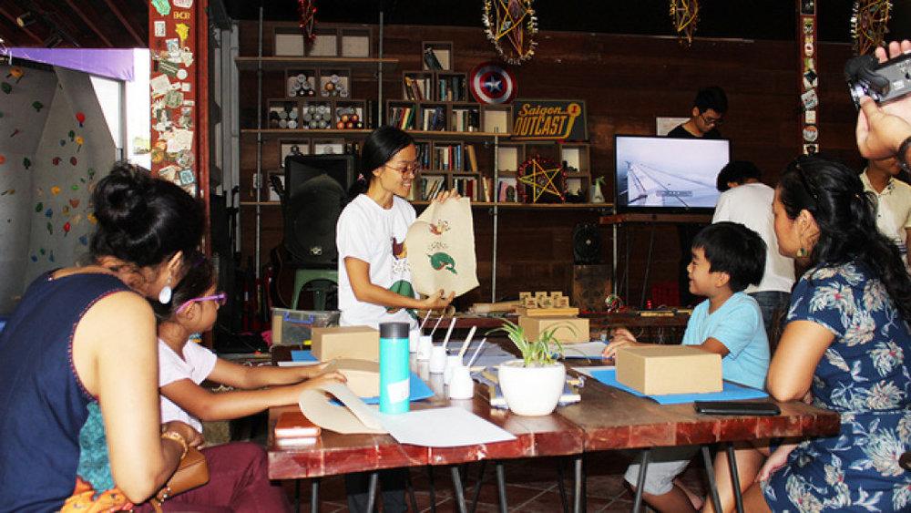 Nguyễn Thị Thanh Mai (đứng) giới thiệu và hướng dẫn các bạn nhỏ và phụ huynh tự in tranh Đông Hồ - Ảnh: Q.L.