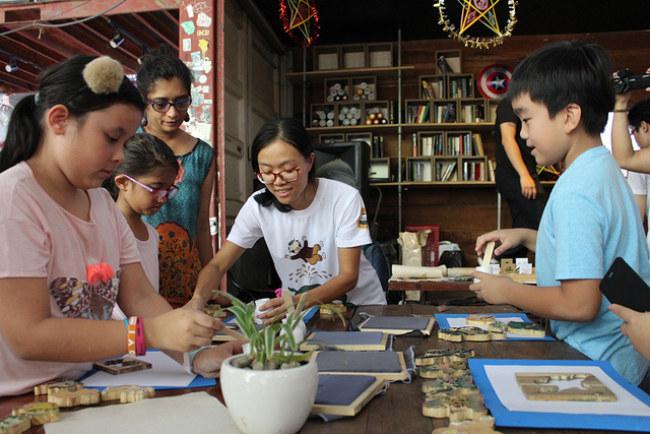 Nguyễn Thị Thanh Mai giới thiệu và hướng dẫn các bạn nhỏ và phụ huynh tự in tranh Đông Hồ - Ảnh: Q.L.