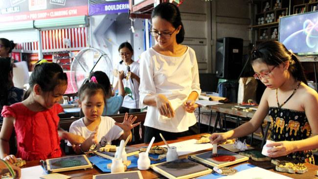 Các bạn nhỏ cùng thử nghiệm tự tay in cho mình bức tranh Đông Hồ yêu thích - Ảnh: Q.L.