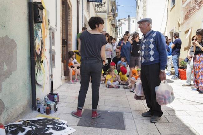 - Zio Nicola – một dân làng – trao đổi với giám đốc nghệ thuật Alice Pasquini, người có ông nội là bác sĩ của làng trong nhiều năm.