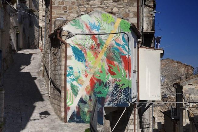Một trong hai bức tường được vẽ bởi Gola Hundun trên nền đất đá, lấy cảm hứng từ môi trường xung quanh làng.
