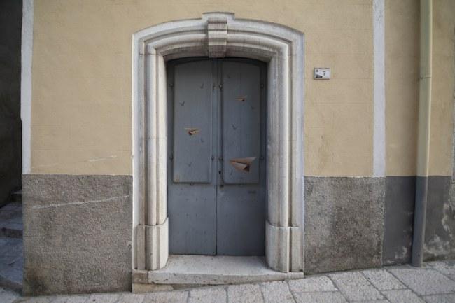 Trở lại Civitacamporano sau khi tham gia dự án vào năm ngoái, nghệ sĩ người Ý UNO tạo ra mô phỏng nghệ thuật gấp giấy trên một cánh cửa cũ.