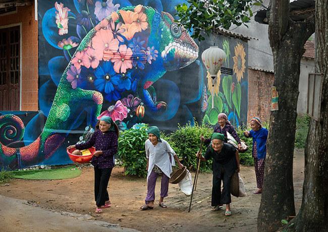 Các cụ già trong làng đi ngang qua bức vẽ mà ban đêm phát sáng tạo ra không gian lung linh, kỳ ảo- Ảnh: LÊ HỒNG LINH