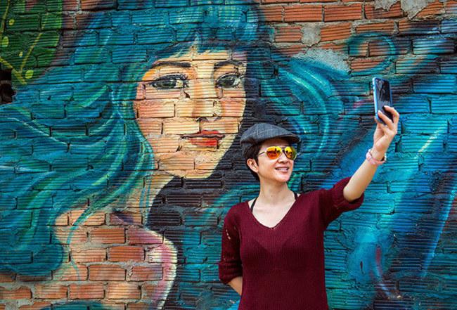 Julie Ho - một bạn trẻ Việt kiều đang sống tại Texas (Hoa Kỳ), tìm đến tham quan và chụp ảnh lưu niệm tại làng Bích họa - Ảnh: LÊ HỒNG LINH
