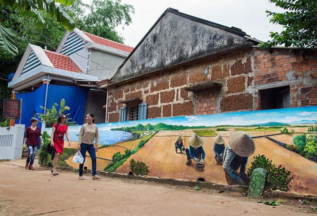 Khách tham quan đang đi qua bức tranh người dân đang trồng hành. Một nghề truyền thống có tiếng tại địa phương - Ảnh: LÊ HỒNG LINH