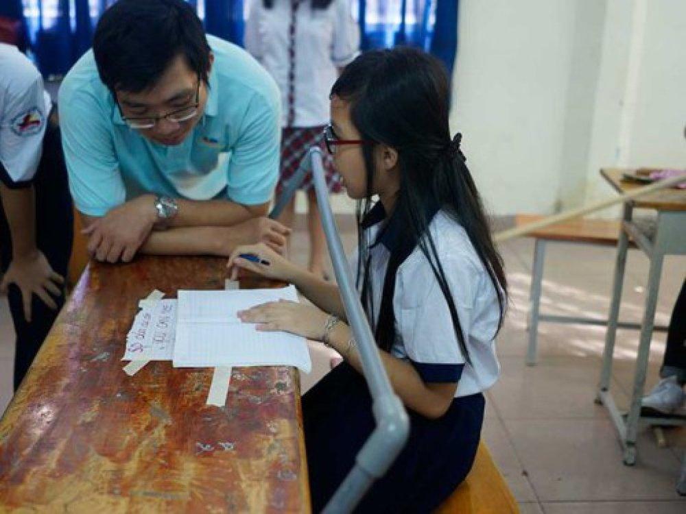Thầy Huỳnh Kiều Viết Lãm cùng trò đang thử nghiệm trên chiếc bàn có thanh ngang phòng tránh cận thị.