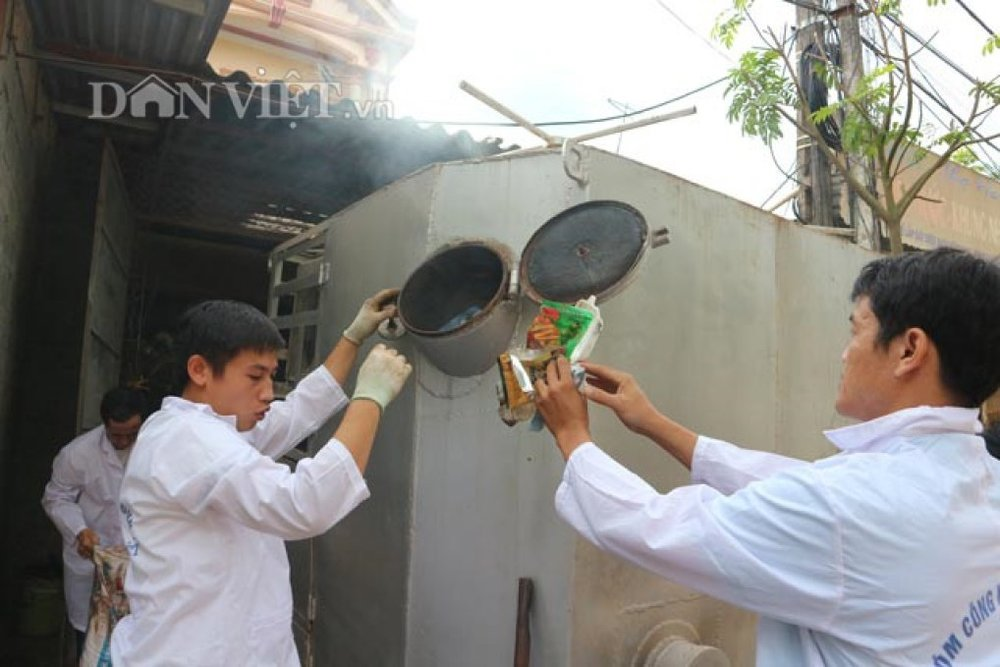 Trưởng Nhóm Kim Cương Việt Tào Nguyên Giáp (trái) và thành viên nhóm đang cho rác vào máy xử lý rác.