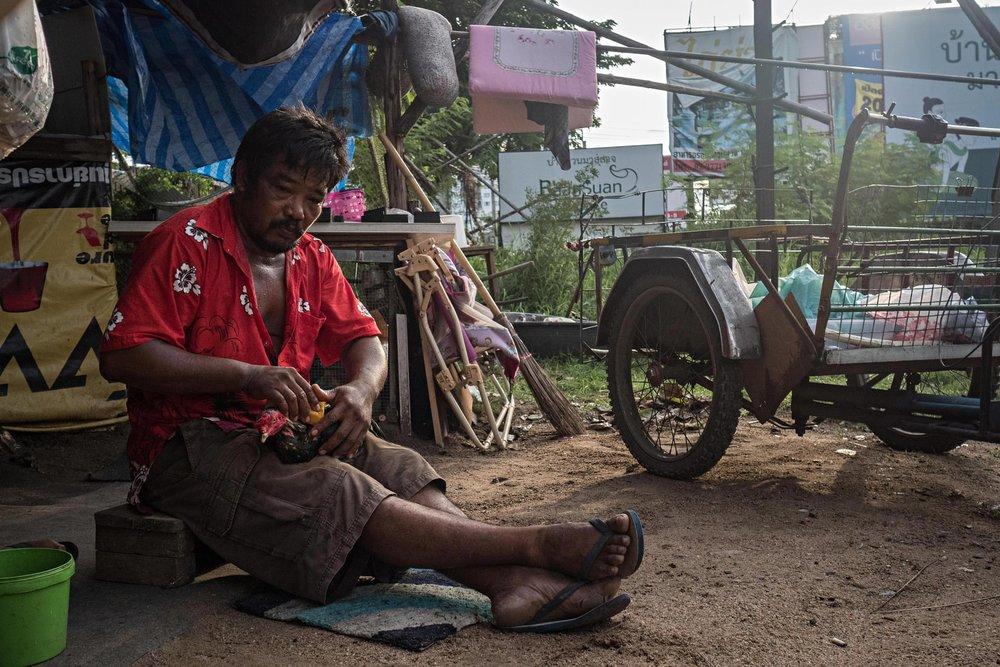 Một người đàn ông đang nghỉ ngơi bên cạnh chiếc xe thu gom rác, nguồn sống của cả gia đình ông.