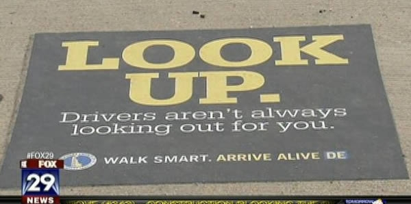 """Các tấm biển cảnh báo dán trên mặt đất - Trên những con đường đông đúc và các ngã tư, các quan chức tại Delaware đặt những tấm biển cảnh báo, trên đó ghi dòng chữ """"Nhìn lên đi. Không phải tài xế nào cũng để ý đến bạn đâu."""""""
