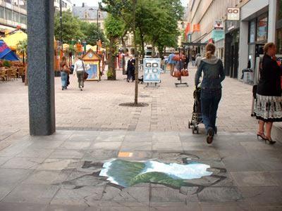 Lòng đất dưới chân bạn đang đi - cách một lớp đá rất mỏng thôi - là cả một vùng núi non sông nước thanh bình. Sáng tạo này được thực hiện bởi nghệ sĩ đường phố Hà Lan tại Rotterdam.
