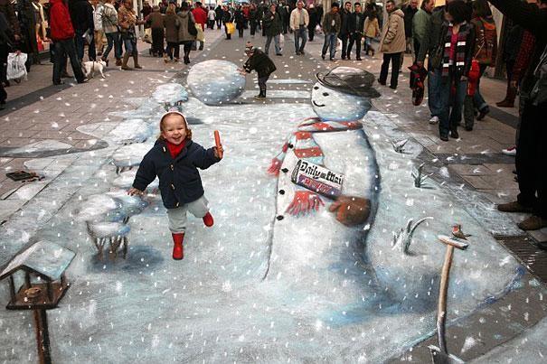 Tuyết chưa rơi nhưng người tuyết đã đến rồi! Tác phẩm của nghệ sĩ Julian Beever người Anh trên một đại lộ ở Bỉ và cũng là một trong những tác phẩm nổi tiếng nhất, bắt đầu cho trào lưu tranh nghệ thuật 3D đường phố từ thập niên 1990.
