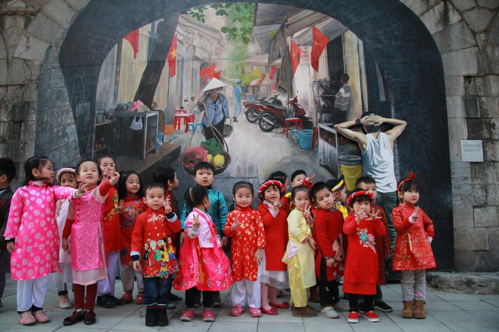 Các bé được cô giáo dẫn đến phố bích họa Phùng Hưng chụp ảnh lưu niệm - Ảnh: DANH TRỌNG