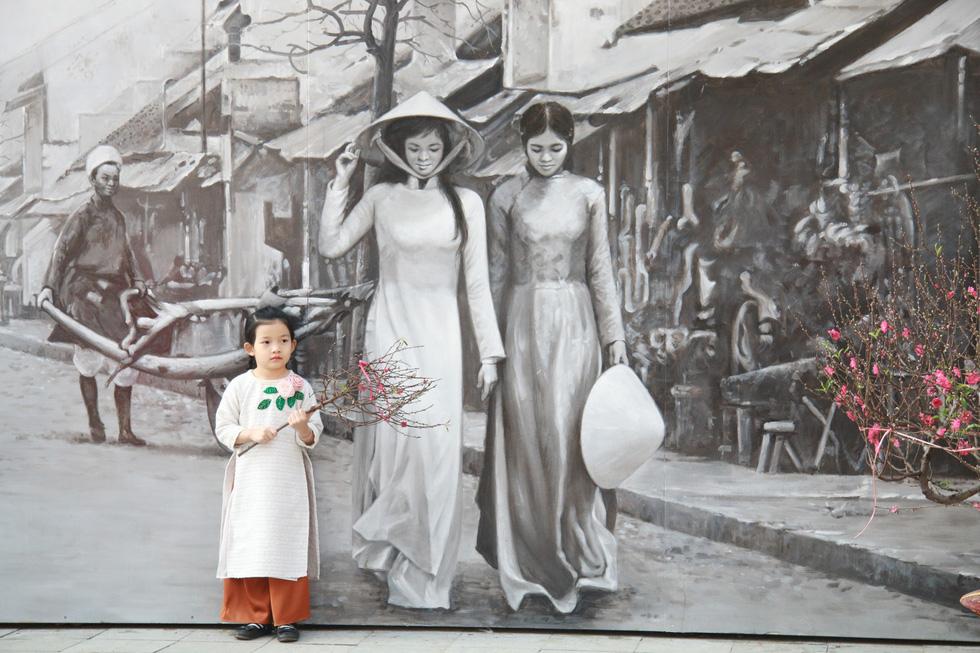 Một cô bé chụp ảnh với bức tranh Phố cổ Hà Nội xưa - Ảnh: DANH TRỌNG