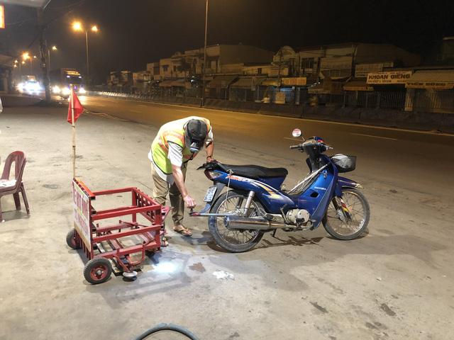 Ông Cảnh đang lắp ráp chiếc xe hút đinh tự chế vào xe máy để thực hiện công việc của mình