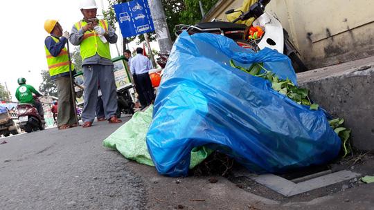 Người dân xả rác sinh hoạt ngay hố ga miệng thu nước trên đường Nguyễn Kiệm (quận Gò Vấp) .
