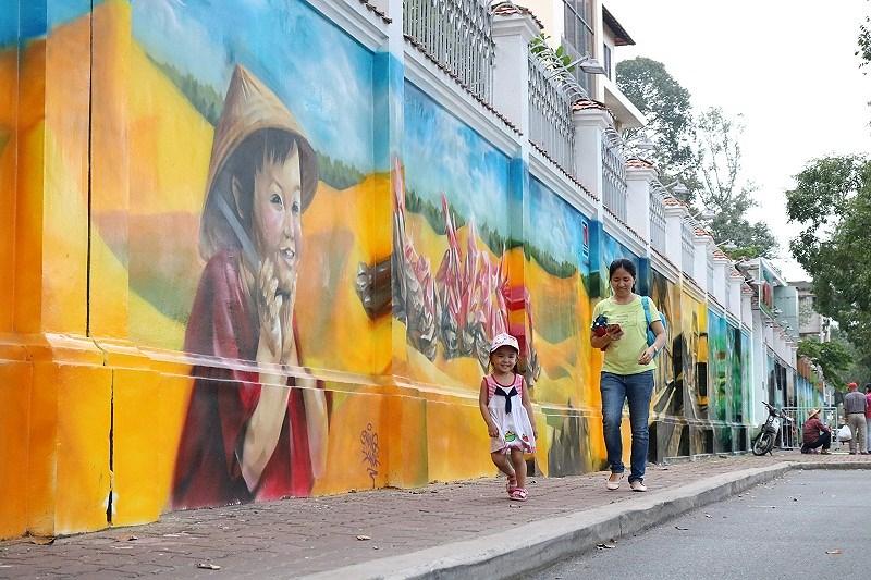 Cô bé sau khi tan trường nhảy nhót trên đường đi, thích thú khi nhìn thấy những bức vẽ  .