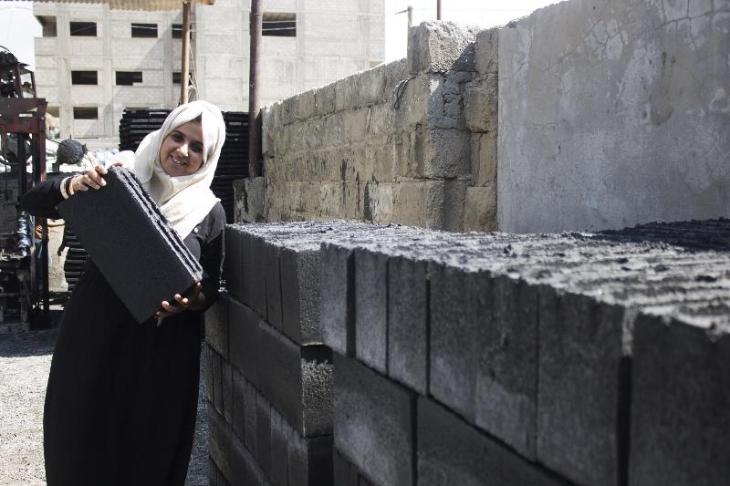 Cô Majd Mashhrawi nâng 1 viên gạch Greencake để chứng minh loại gạch này nhẹ hơn gạch nung truyền thống ra sao.