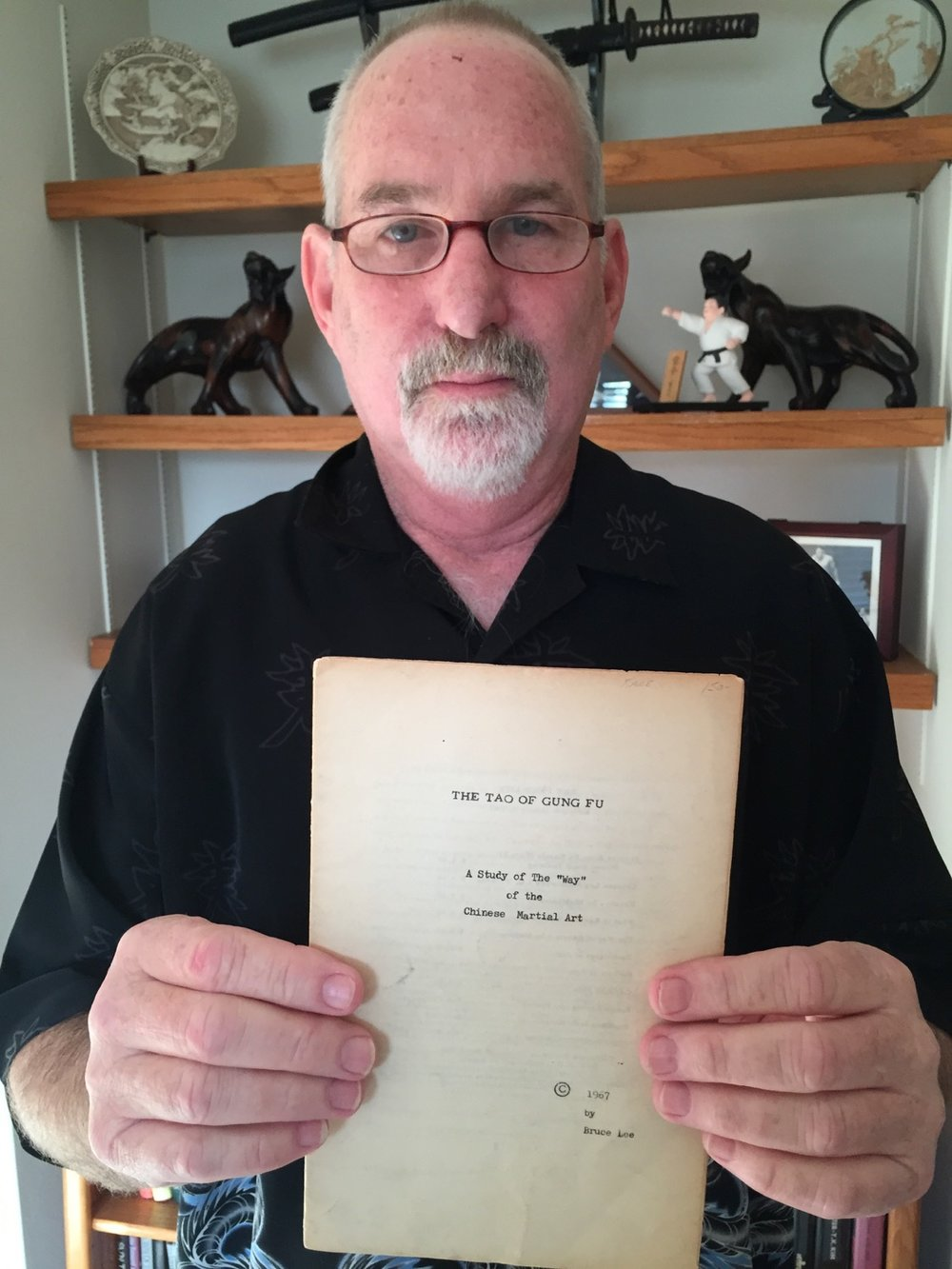 Jon Wiedenman poses with his original copy of a 1967 Bruce Lee essay.