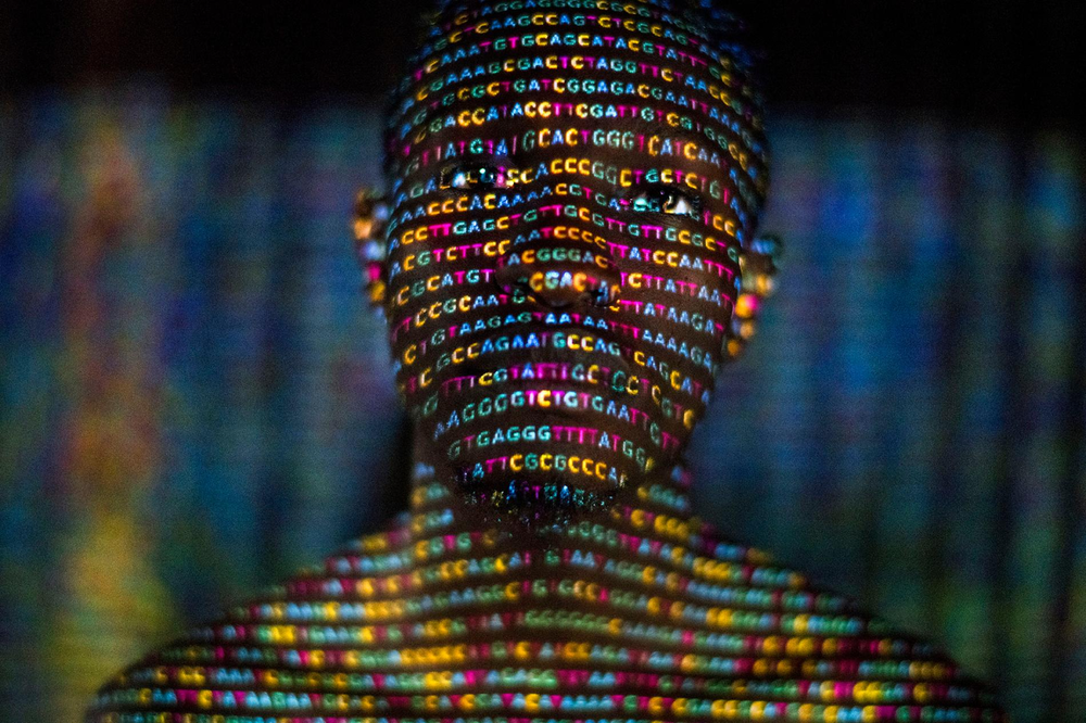 A silhouetted person with the G's, A's, T's, and C's that encode their genetic sequence overlaid